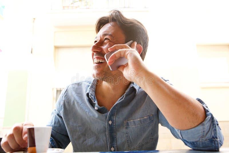 Εύθυμο ώριμο άτομο που μιλά στο κινητό τηλέφωνο στη καφετερία στοκ φωτογραφία με δικαίωμα ελεύθερης χρήσης