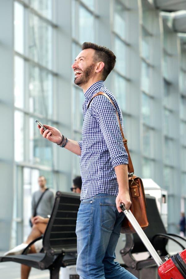 Εύθυμο ώριμο άτομο που περπατά με την τσάντα και το κινητό τηλέφωνο στοκ φωτογραφίες με δικαίωμα ελεύθερης χρήσης