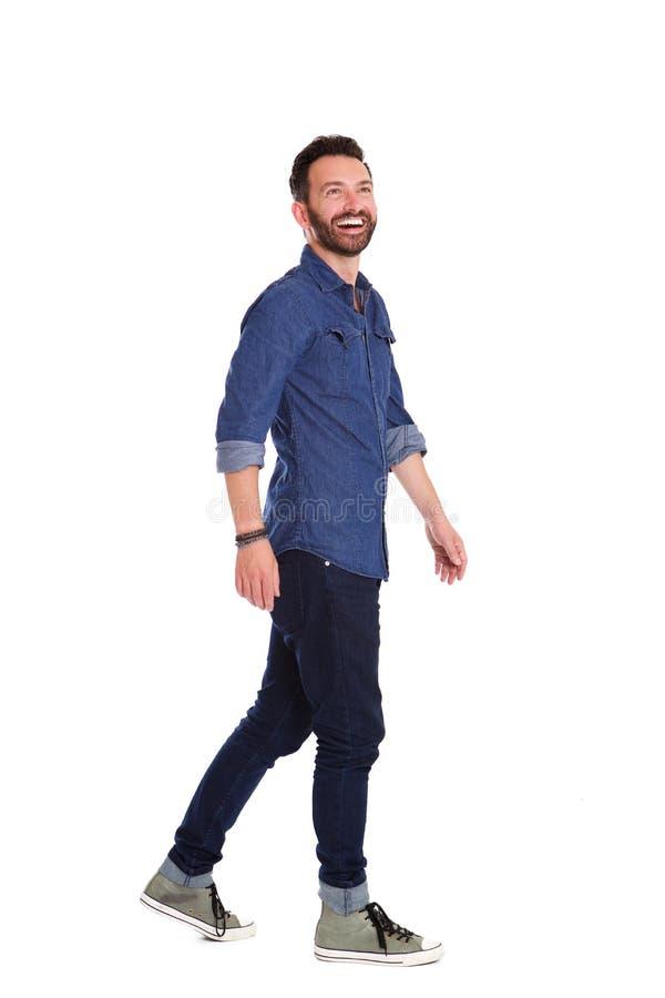 Εύθυμο ώριμο άτομο που περπατά πέρα από το άσπρο υπόβαθρο στοκ φωτογραφία με δικαίωμα ελεύθερης χρήσης
