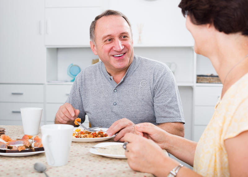 Εύθυμο ώριμο άτομο που τρώει το μεσημεριανό γεύμα στο σπίτι στοκ εικόνες