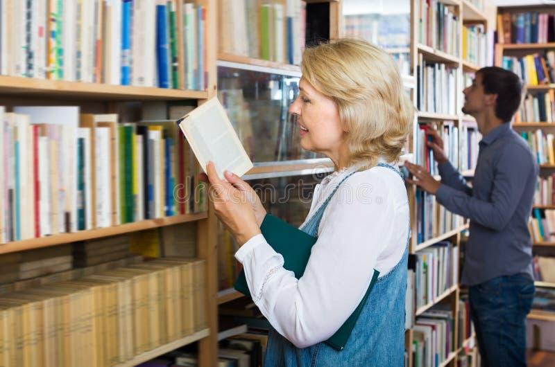 Εύθυμο ώριμο βιβλίο ανάγνωσης γυναικών στο κατάστημα βιβλίων στοκ εικόνα με δικαίωμα ελεύθερης χρήσης