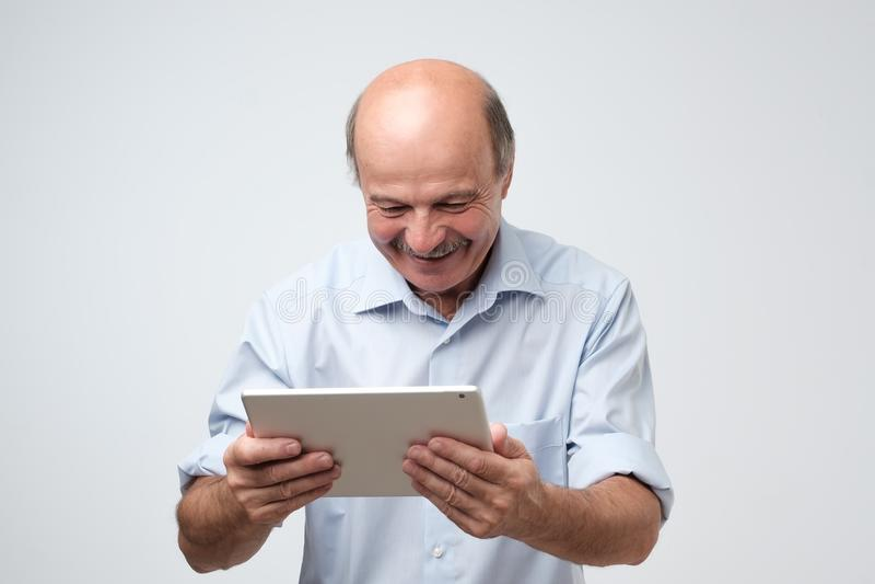 Εύθυμο ώριμο ευρωπαϊκό άτομο που εργάζεται στις ψηφιακές καλές ειδήσεις ανάγνωσης χαμόγελου ταμπλετών στοκ εικόνες
