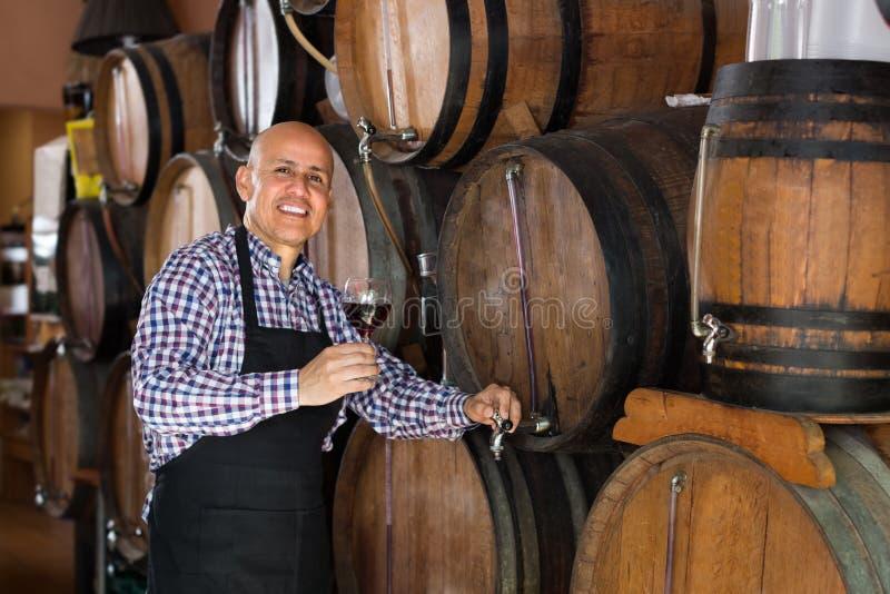 Εύθυμο ώριμο κρασί πλήρωσης πωλητών ατόμων από το ξύλο στοκ εικόνες