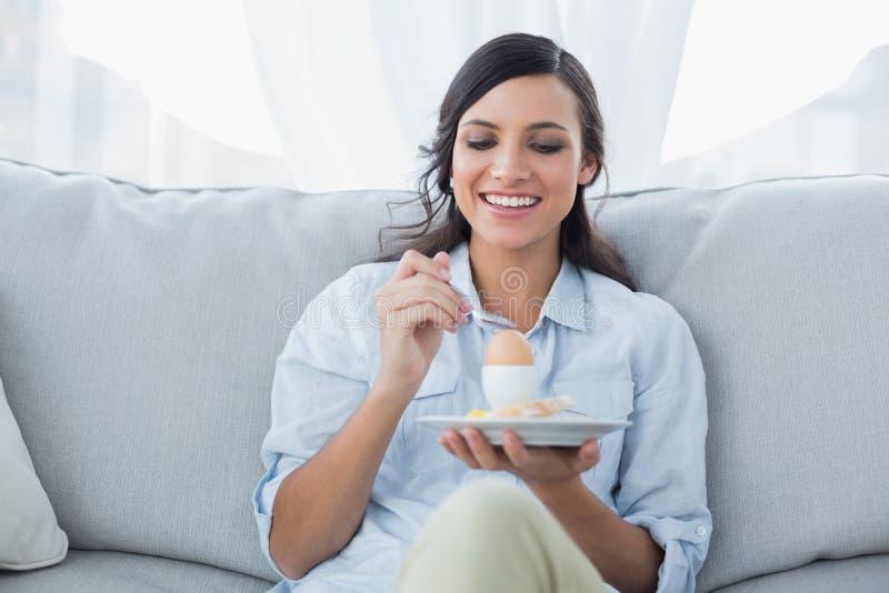 Εύθυμο brunette που τρώει το αυγό στοκ φωτογραφία με δικαίωμα ελεύθερης χρήσης