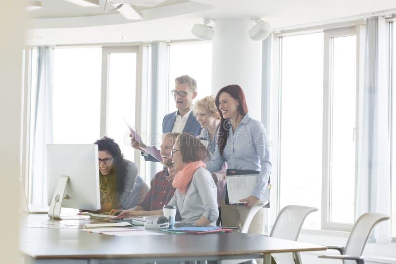 Εύθυμο businesspeople που λειτουργεί μαζί στον πίνακα διασκέψεων στοκ φωτογραφία με δικαίωμα ελεύθερης χρήσης