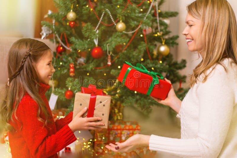 Εύθυμο mom και το χαριτωμένο κορίτσι κορών της που ανταλλάσσουν τα δώρα Χριστούγεννα καλές διακ& στοκ φωτογραφίες με δικαίωμα ελεύθερης χρήσης