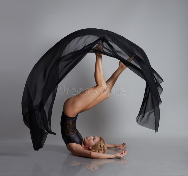 Εύκαμπτη τοποθέτηση κοριτσιών με το μαύρο πετώντας ύφασμα στοκ εικόνα