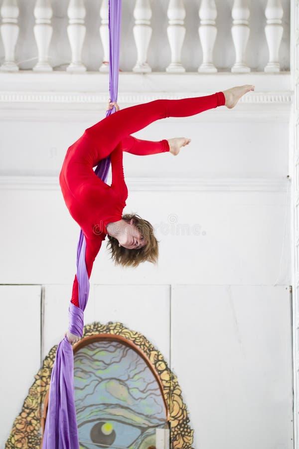 Εύκαμπτος ελκυστικός gymnast αέρα γυναικών εκτελεί μια άσκηση στο εναέριο μετάξι στοκ φωτογραφία με δικαίωμα ελεύθερης χρήσης