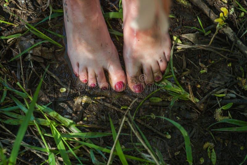 Εύμορφα πόδια κοριτσιών στη λάσπη στοκ φωτογραφία