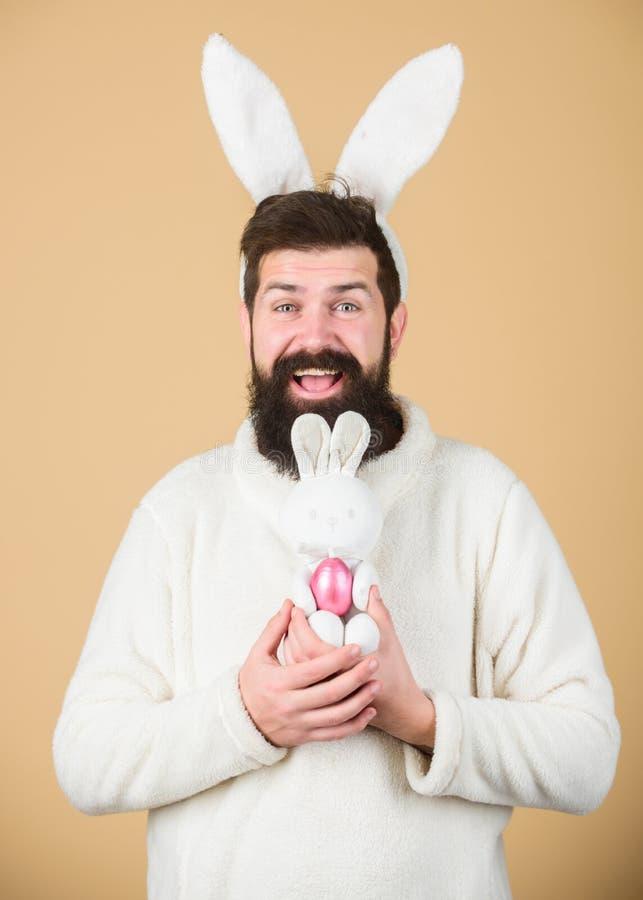 Εύφορος και παραγωγικός Hipster με τα μακριά αυτιά κουνελιών που κρατούν το αυγό που βάζει τους λαγούς Λαγουδάκι Πάσχας που παραδ στοκ φωτογραφίες με δικαίωμα ελεύθερης χρήσης