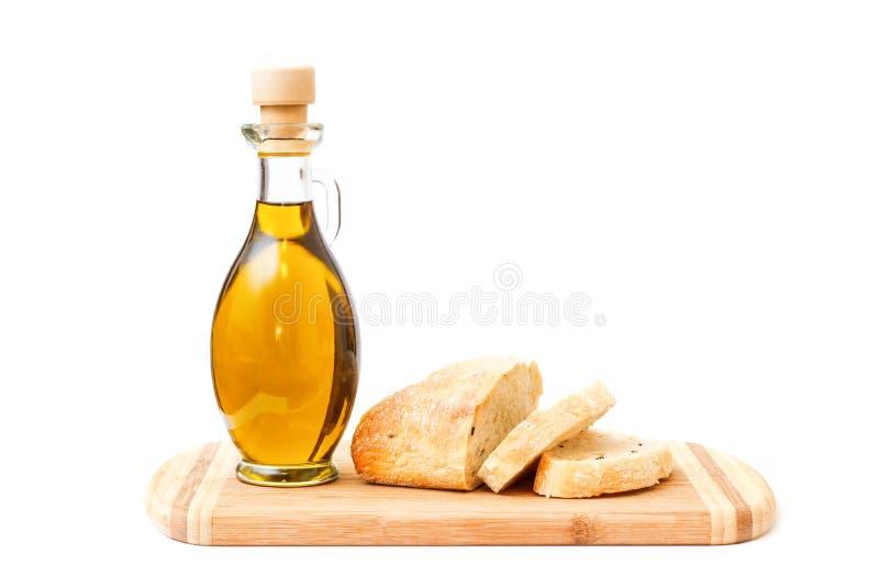 Ελαιόλαδο και τεμαχισμένο ψωμί στον τέμνοντα πίνακα στοκ φωτογραφίες