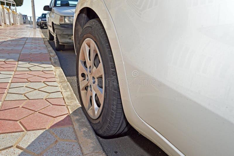 Ελαστικό αυτοκινήτου αυτοκινήτων ενάντια σε μια συγκράτηση σε ένα πεζοδρόμιο στοκ εικόνες