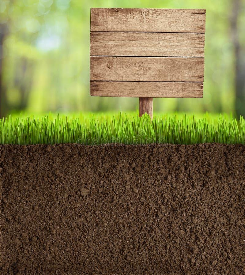 Εδαφολογική περικοπή στον κήπο με το ξύλινο σημάδι στοκ εικόνες