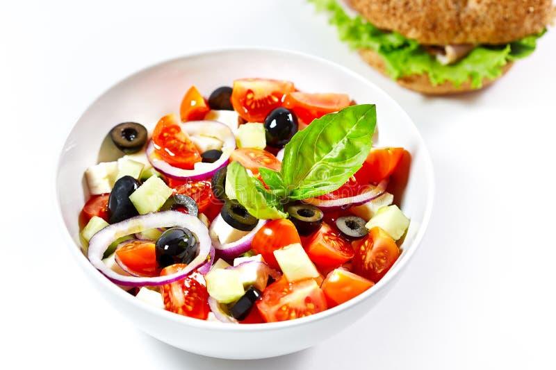 Ελαφριά ελληνική σαλάτα με τα φρέσκα λαχανικά και burger στην πλάτη στοκ εικόνες