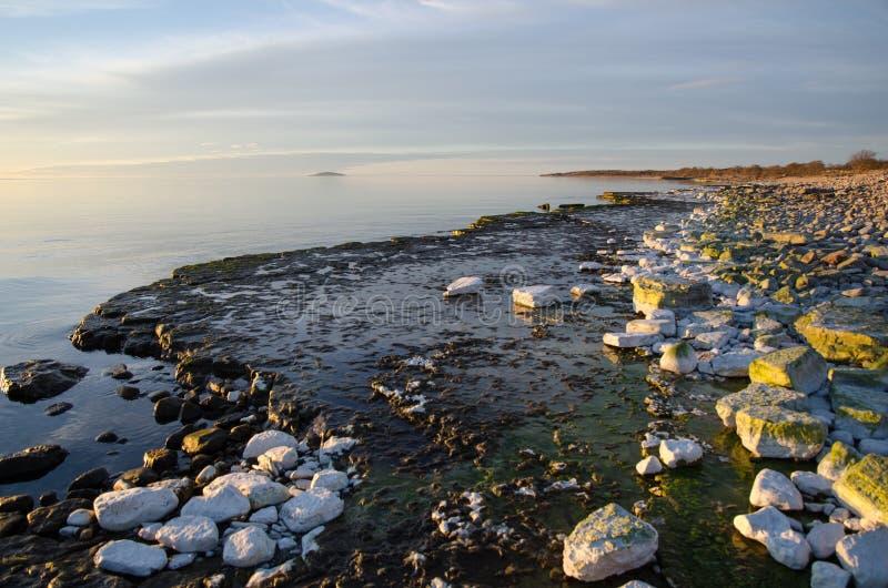 Ελαφριά χρώματα βραδιού από μια επίπεδη ακτή βράχου στοκ εικόνες