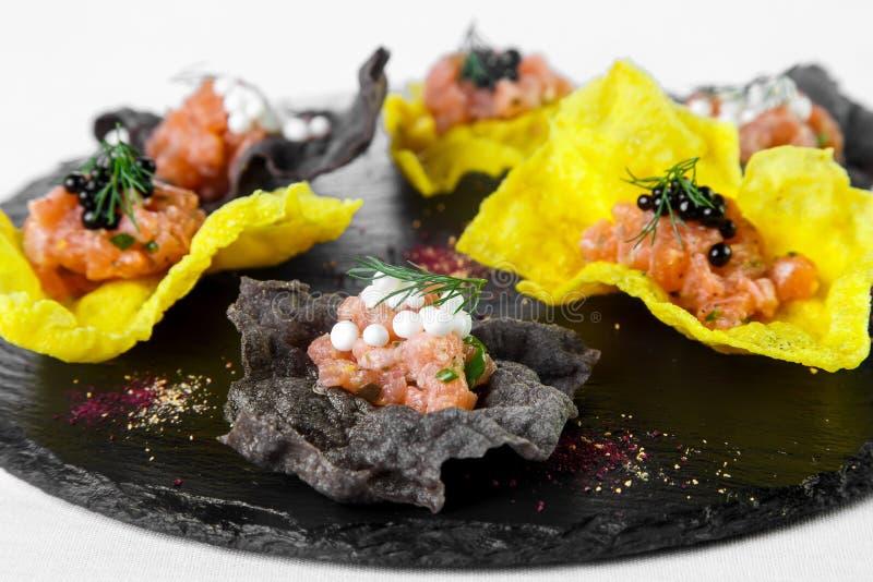 Ελαφρύ πρόχειρο φαγητό των μαύρων και κίτρινων τσιπ που γεμίζουν με τα θαλασσινά στο sto στοκ εικόνα με δικαίωμα ελεύθερης χρήσης