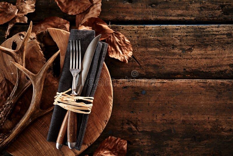 Ελαφόκερες ελαφιών με τα μαχαιροπήρουνα στον ξύλινο πίνακα στοκ εικόνα