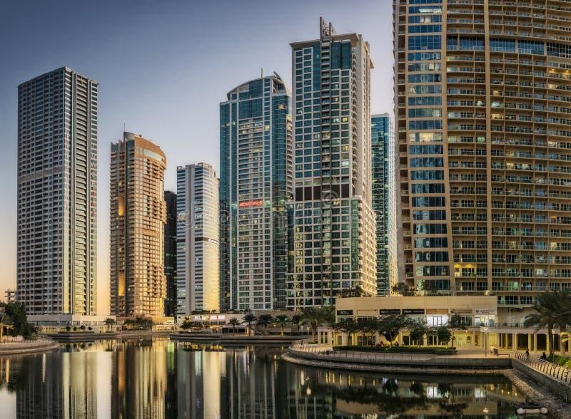 Ε.Α.Ε. ΝΤΟΥΜΠΆΙ - 20 DEZ 2018 - πόλη scape του Ντουμπάι με τον ουρανοξύστη στο ηλιοβασίλεμα και την αντανάκλαση στο νερό στοκ φωτογραφία με δικαίωμα ελεύθερης χρήσης