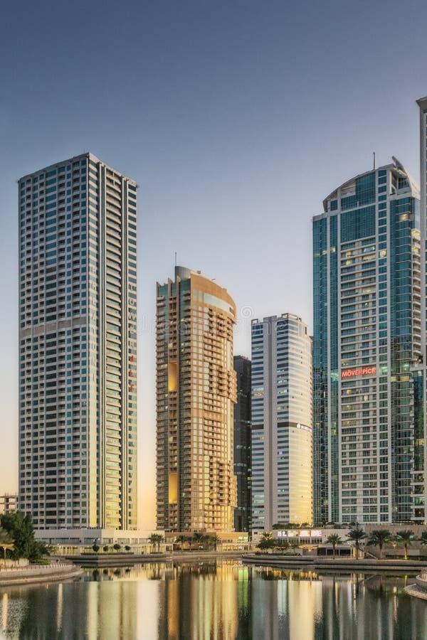 Ε.Α.Ε. ΝΤΟΥΜΠΆΙ - 20 DEZ 2018 - πόλη scape του Ντουμπάι με τον ουρανοξύστη στο ηλιοβασίλεμα και την αντανάκλαση στο νερό στοκ εικόνα