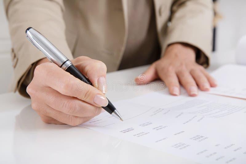 Ελεγκτής που αναλύει τις δαπάνες και το εισόδημα με μια μάνδρα και έναν έλεγχο μΑ στοκ φωτογραφία