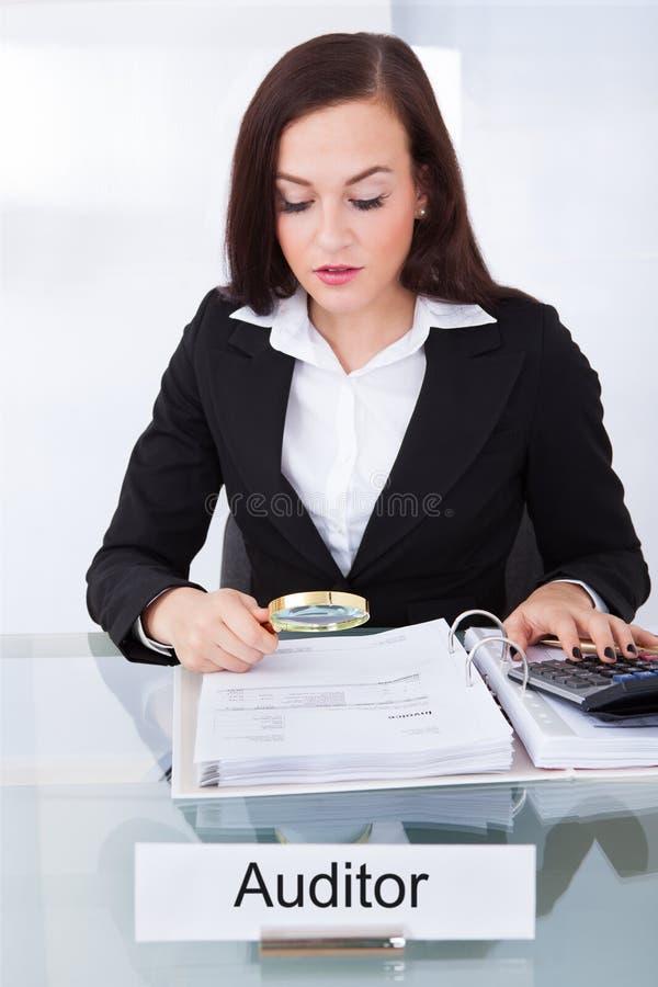 Ελεγκτής που διερευνά τα οικονομικά έγγραφα στοκ εικόνα με δικαίωμα ελεύθερης χρήσης