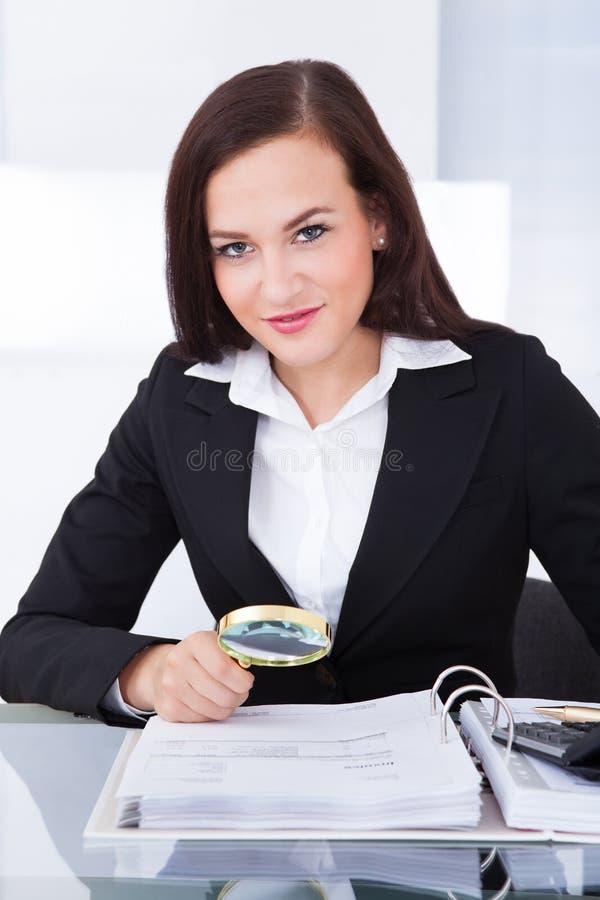 Ελεγκτής που διερευνά τα οικονομικά έγγραφα στοκ εικόνες