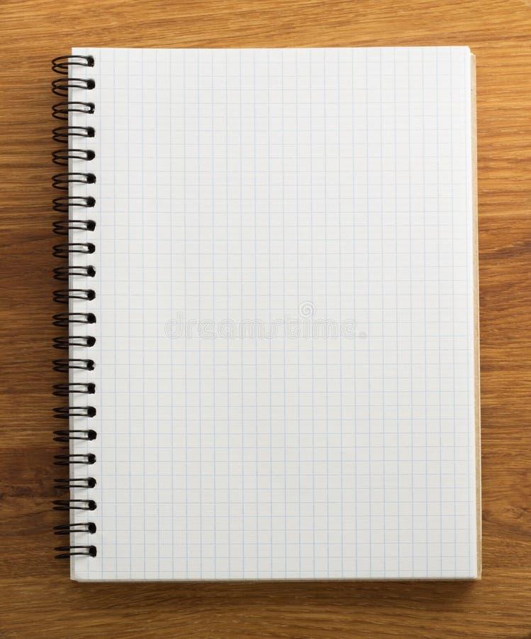 Ελεγχμένο σημειωματάριο στο ξύλο στοκ φωτογραφίες