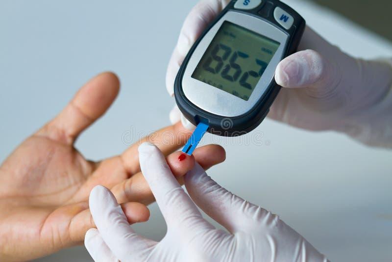 ελεγχόμενος αίμα μετρητής γλυκόζης γιατρών στοκ εικόνα