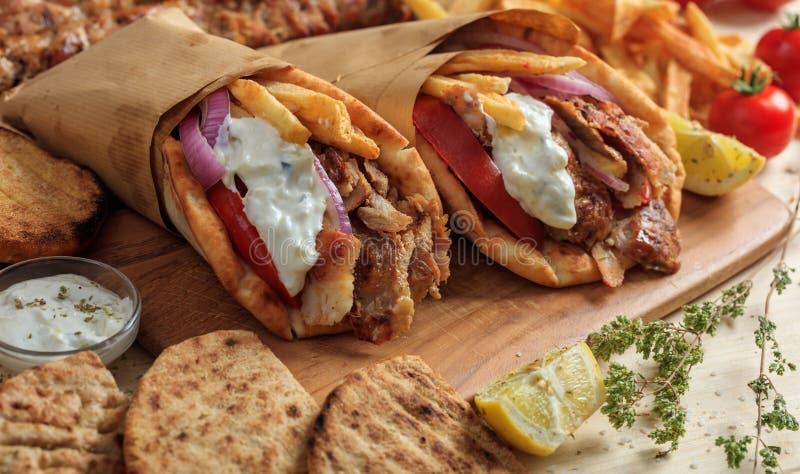 Ελληνικά γυροσκόπια που τυλίγονται στα ψωμιά pita σε έναν ξύλινο πίνακα στοκ εικόνα