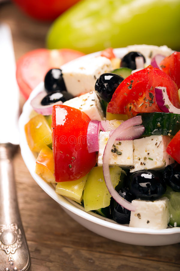 Ελληνική σαλάτα με τα φρέσκα λαχανικά, το τυρί φέτας και τις μαύρες ελιές κλείστε επάνω στοκ εικόνα