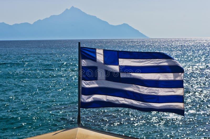 Ελληνική σημαία σε ένα πλέοντας σκάφος με το ιερό βουνό Athos στο υπόβαθρο στοκ εικόνες