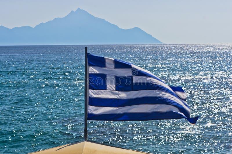 Ελληνική σημαία σε ένα πλέοντας σκάφος με το ιερό βουνό Athos στο υπόβαθρο στοκ εικόνες με δικαίωμα ελεύθερης χρήσης