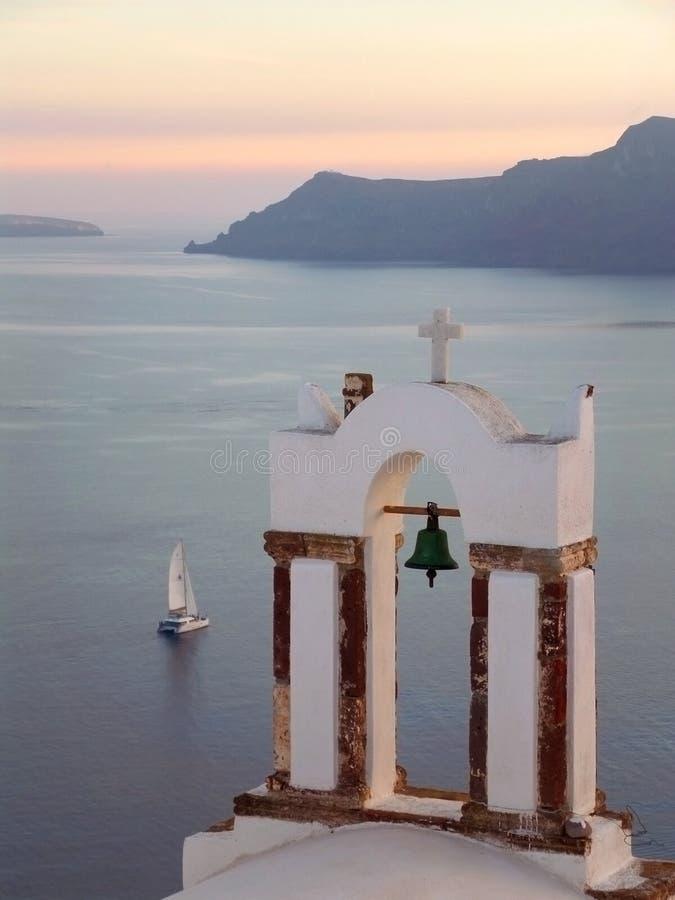 Ελληνικός πύργος κουδουνιών Ορθόδοξων Εκκλησιών ενάντια στο Αιγαίο πέλαγος με την πλέοντας βάρκα στο ηλιοβασίλεμα, Santorini στοκ φωτογραφία με δικαίωμα ελεύθερης χρήσης