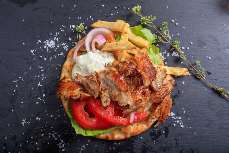 Ελληνικό πιάτο γυροσκοπίων σε ένα μαύρο πιάτο - τοπ άποψη στοκ εικόνες