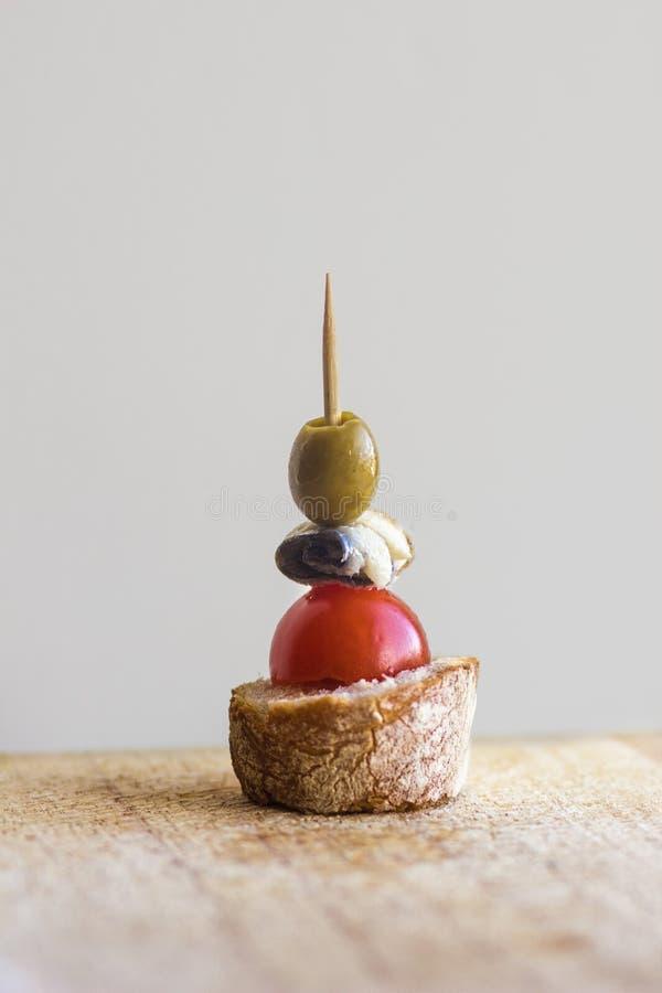 Ελιά Pintxo, αντσούγια, ντομάτα κερασιών και ψωμί σε έναν αγροτικό πίνακα στοκ εικόνες