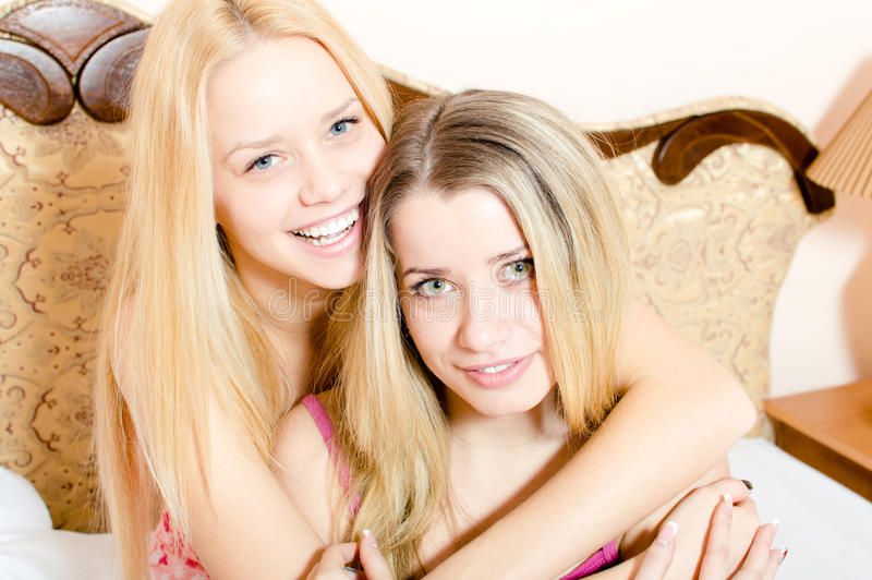 2 ελκυστικές ξανθές νέες όμορφες φίλες γυναικών στις πυτζάμες που έχουν τη διασκέδαση που αγκαλιάζει τη συνεδρίαση στο άσπρο ευτυ στοκ εικόνες
