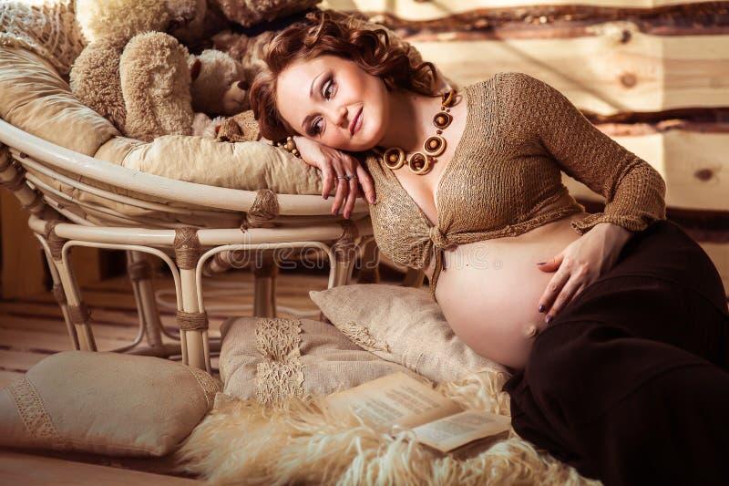 Ελκυστική έγκυος γυναίκα που βρίσκεται στη γούνα με ένα βιβλίο στοκ φωτογραφία με δικαίωμα ελεύθερης χρήσης