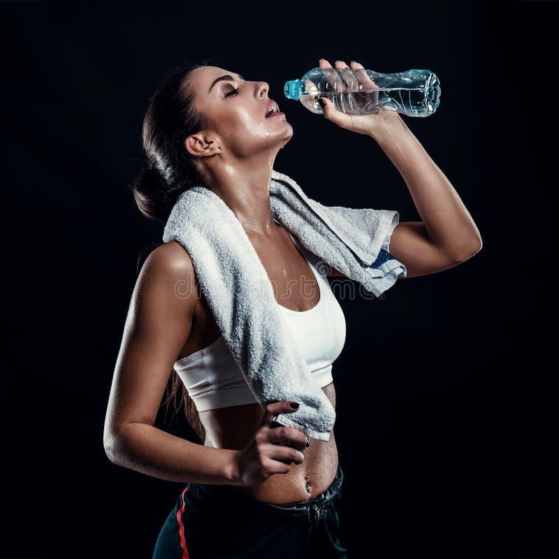 Ελκυστική αθλητική νέα γυναίκα με το τέλειο πόσιμο νερό σωμάτων από ένα μπουκάλι με την πετσέτα γύρω από το λαιμό της στο μαύρο κ στοκ φωτογραφία με δικαίωμα ελεύθερης χρήσης