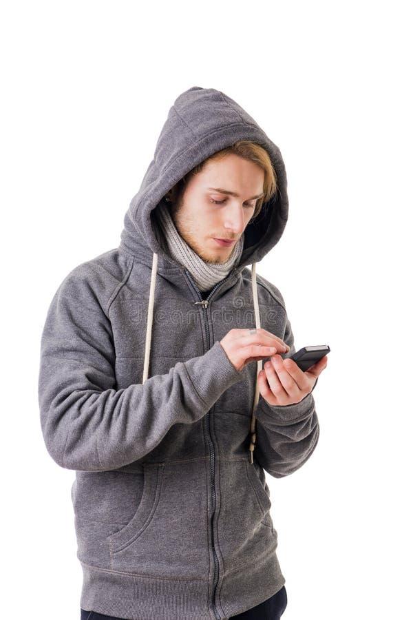 Ελκυστική δακτυλογράφηση νεαρών άνδρων στο smartphone, που στέλνει το μήνυμα κειμένου στοκ εικόνα