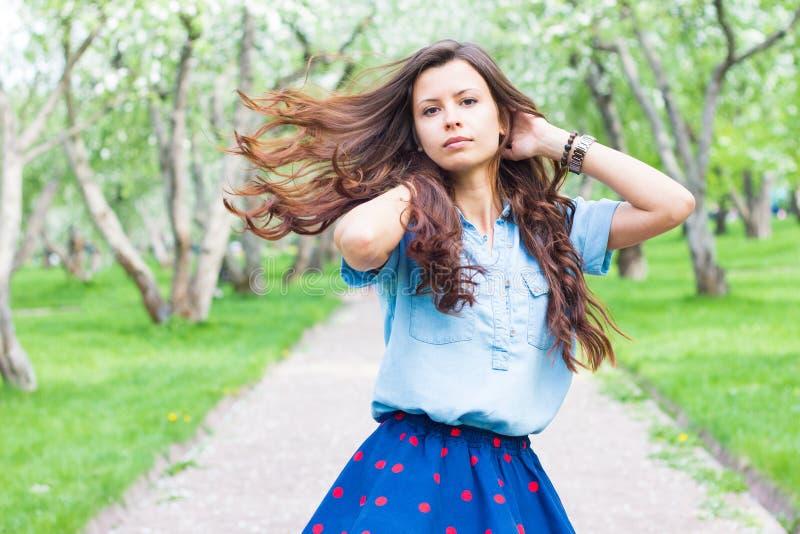 Ελκυστική γυναίκα με την περιστροφή τρίχας πετάγματος στο πάρκο στοκ εικόνες