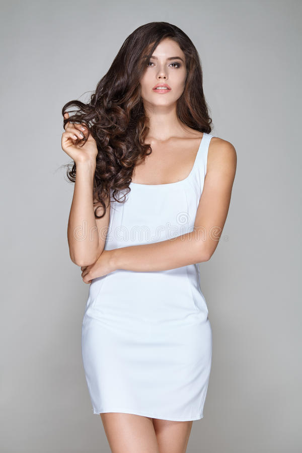 Ελκυστική γυναίκα με τη σγουρή τρίχα στο άσπρο κοντό φόρεμα στοκ φωτογραφίες