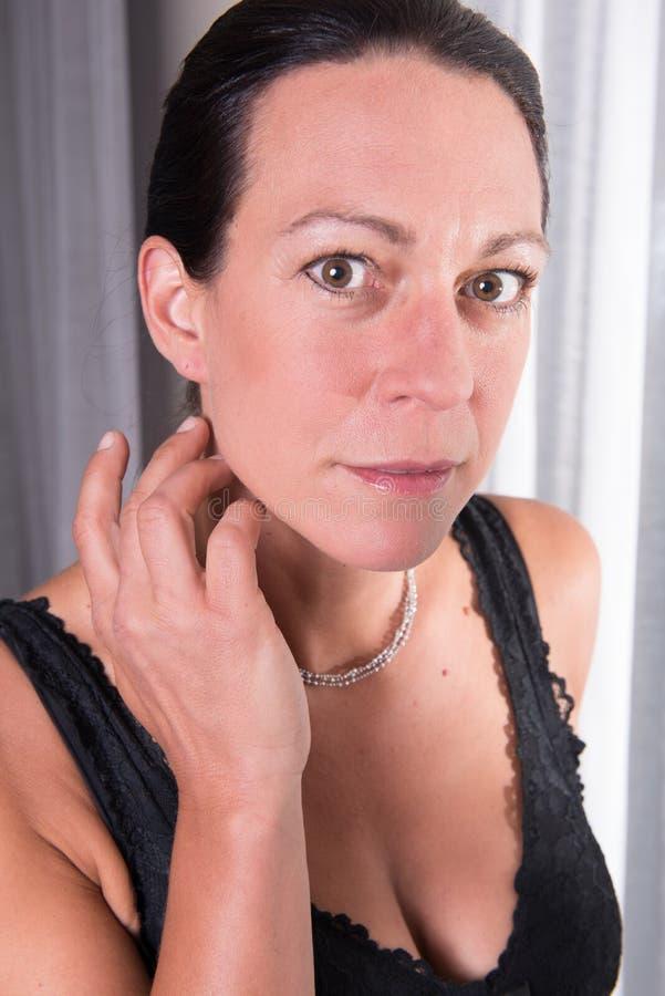 Ελκυστική γυναίκα πορτρέτου με τη μαύρη τρίχα στοκ εικόνα