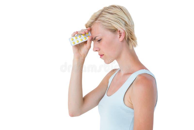 Ελκυστική γυναίκα που έχει τον πονοκέφαλο και που κρατά το πακέτο των χαπιών στοκ φωτογραφία