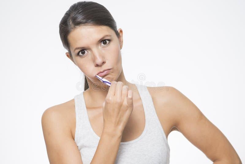 Ελκυστική γυναίκα που βουρτσίζει τα δόντια της στοκ εικόνες