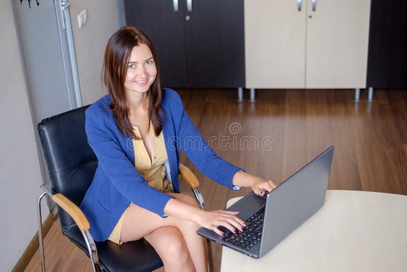 Ελκυστική γυναίκα που εργάζεται στο lap-top στο γραφείο ξεκινήματος στοκ εικόνες