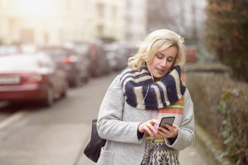 Ελκυστική γυναίκα που ελέγχει την κινητή σε μια οδό στοκ εικόνες