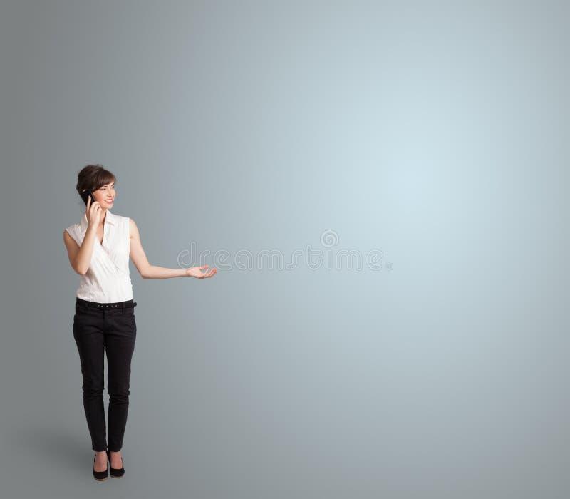 Ελκυστική γυναίκα που κάνει το τηλεφώνημα με το διάστημα αντιγράφων στοκ φωτογραφία με δικαίωμα ελεύθερης χρήσης
