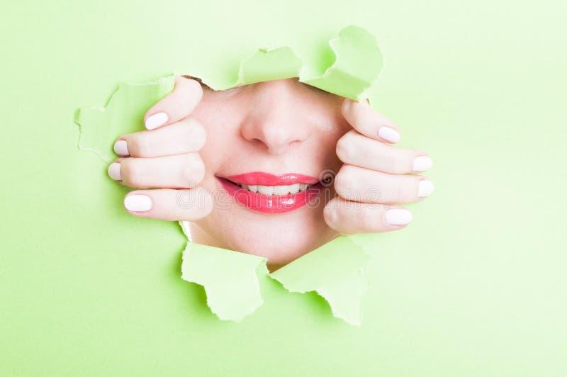 Ελκυστική γυναίκα που παρουσιάζει όμορφο χαμόγελο μέσω του σχισμένου πράσινου cardboa στοκ εικόνες με δικαίωμα ελεύθερης χρήσης