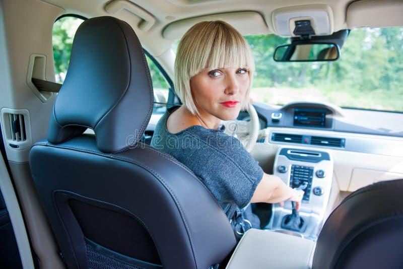 Ελκυστική γυναίκα που σταθμεύει το αυτοκίνητό της στοκ εικόνα