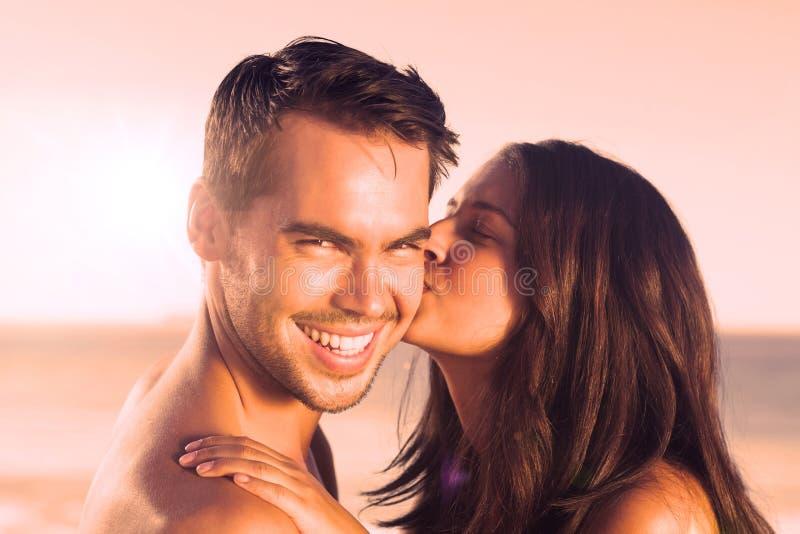 Ελκυστική γυναίκα που φιλά το φίλο της στο μάγουλο ελεύθερη απεικόνιση δικαιώματος